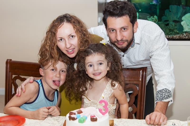 Family celebrating child's birthday. Happy family of four persons, birthday celebration, happy little birthday girl sitting at table with birthday cake, elder royalty free stock photos