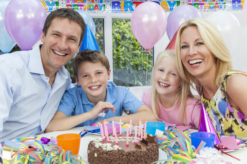 Family Celebrating Children's Birthday Party Cake. Happy family, mother, father, son & daughter celebrating a children's birthday party with the cake stock photography