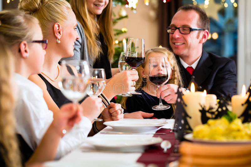 Family celebrating Christmas dinner. German parents and children toasting with wine and water at Christmas eve dinner royalty free stock photo