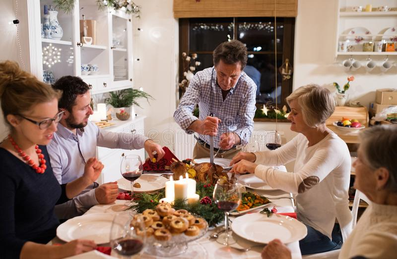 Family celebrating Christmas. Father serving food. royalty free stock photography