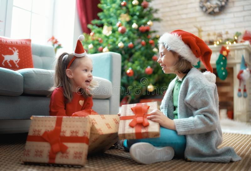Family celebrating Christmas. Merry Christmas and Happy Holidays! Cheerful cute childrens girls opening gifts. Kids are having fun near tree in the morning royalty free stock photos