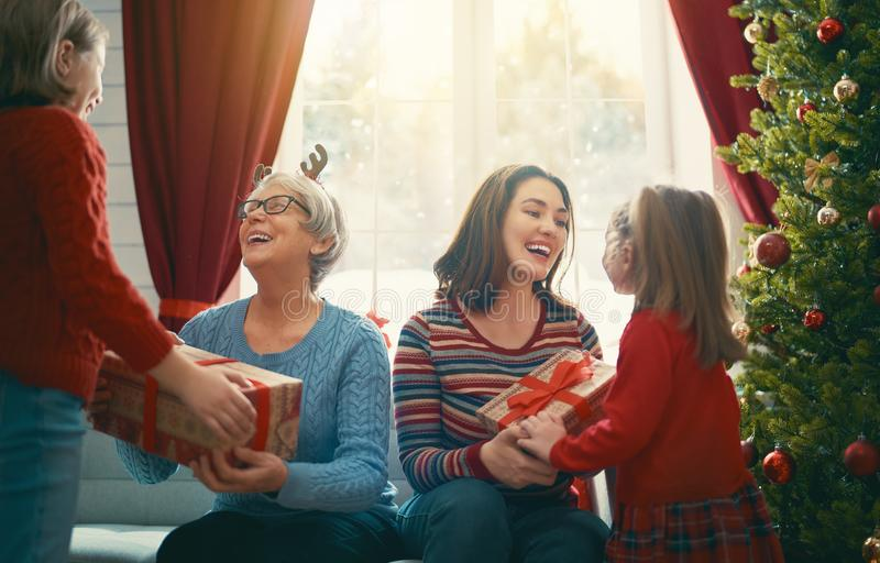 Family celebrating Christmas. Merry Christmas and Happy Holidays! Cheerfuids presenting gifts to mom and granny. Parents and little children having fun near tree royalty free stock photography