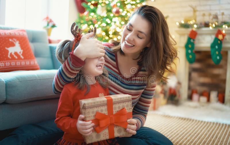 Family celebrating Christmas. Merry Christmas and Happy Holidays! Cheerful mom and her cute daughter girl exchanging gifts. Parent and little child having fun stock photography