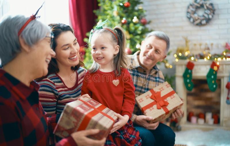 Family celebrating Christmas. Merry Christmas and Happy Holidays! Grandma, grandpa, mum and childr exchanging gifts and having fun near tree indoors. Loving royalty free stock image