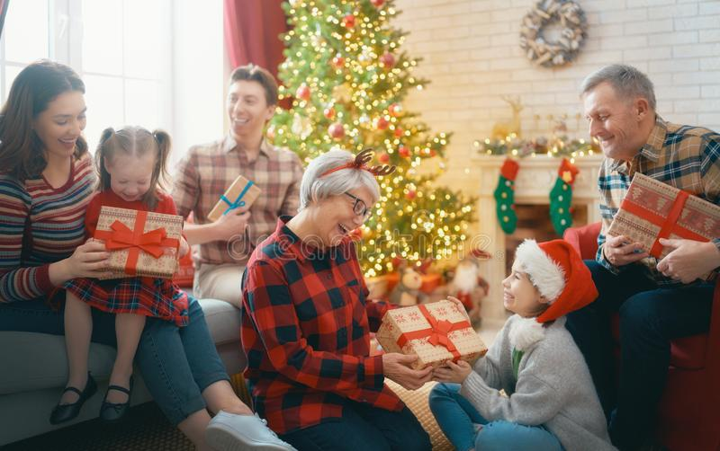 Family celebrating Christmas. Merry Christmas and Happy Holidays! Grandma, grandpa, mum, dad and children exchanging gifts. Parents and daughters having fun near stock photos