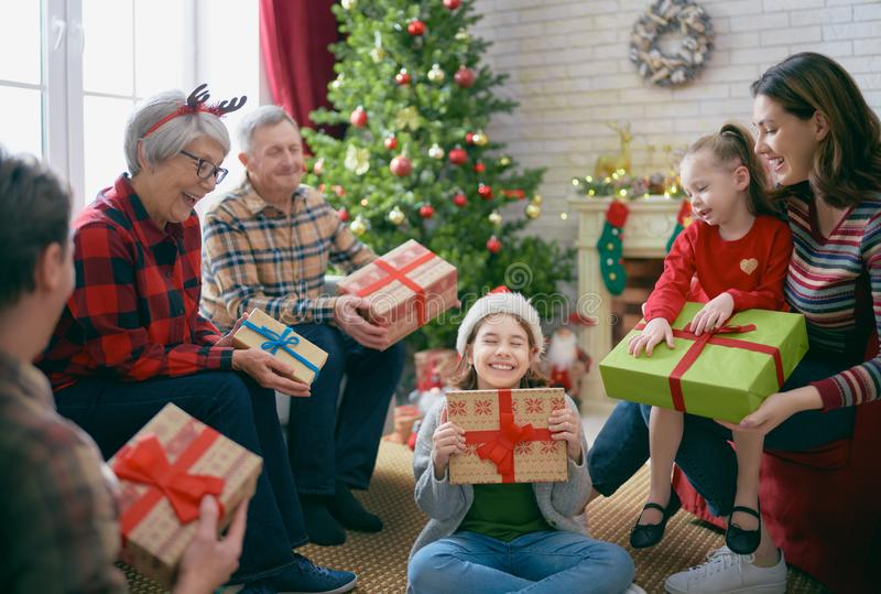 Family celebrating Christmas. Merry Christmas and Happy Holidays! Grandma, grandpa, mum, dad and children exchanging gifts. Parents and daughters having fun near stock photo