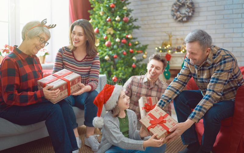 Family celebrating Christmas. Merry Christmas and Happy Holidays! Grandma, grandpa, mum, dad and children exchanging gifts. Parents and daughters having fun near royalty free stock photo