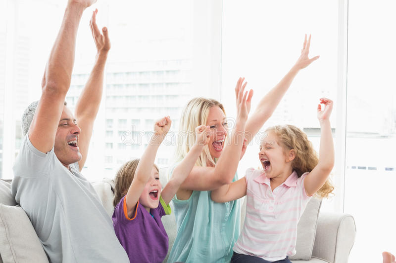 Family celebrating success while watching TV royalty free stock photography