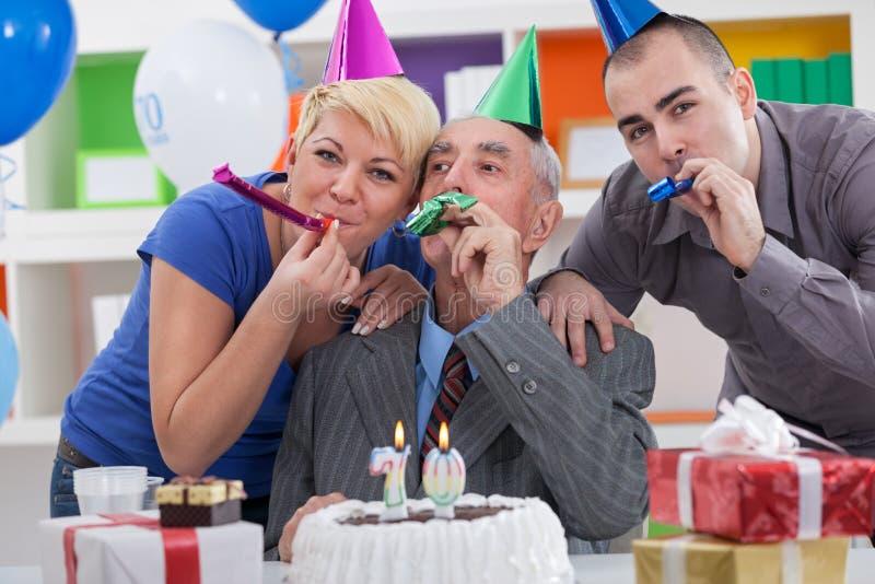 Family celebrating 70th birthday. Happy family together celebrating 70th birthday royalty free stock photography