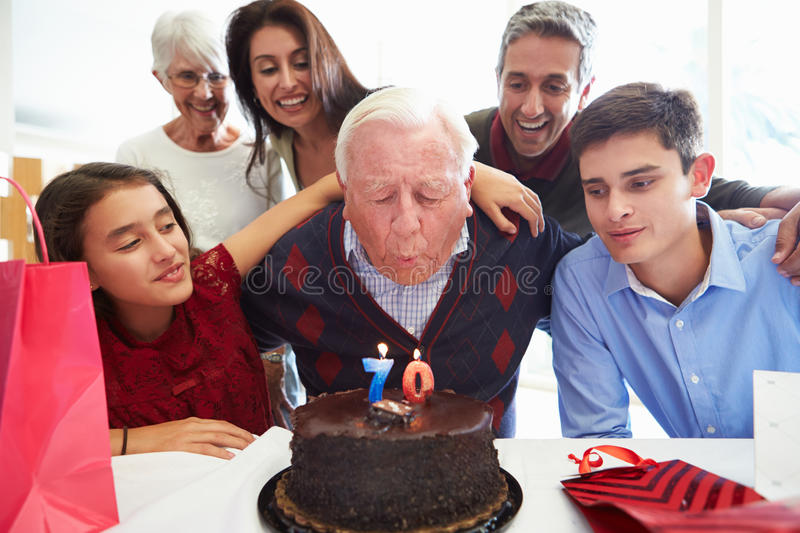 Family Celebrating 70th Birthday Together. Blowing Out Candles On Chocolate Cake stock photos