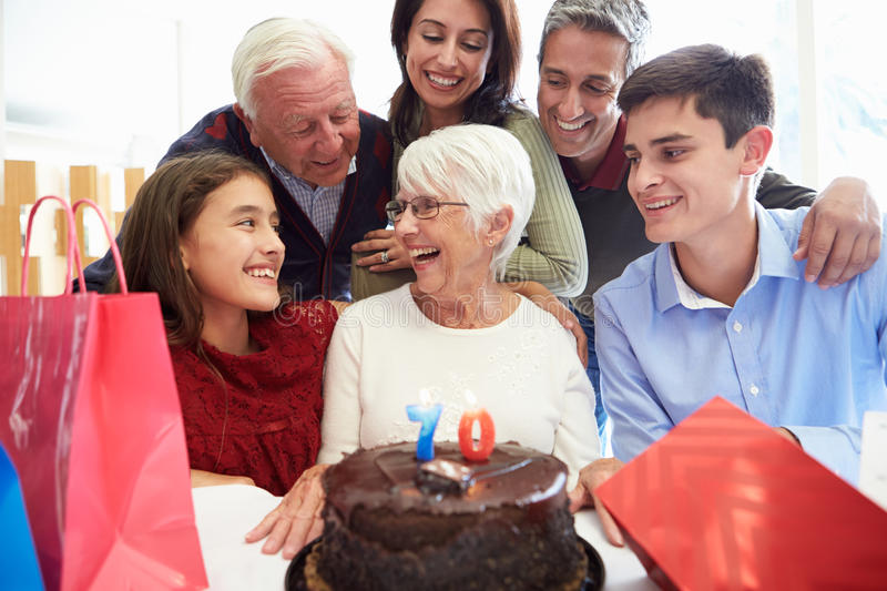 Family Celebrating 70th Birthday Together. With Birthday Cake Smiling At Each Other stock photography