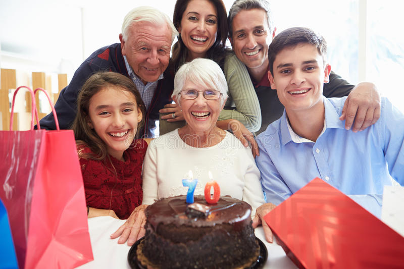 Family Celebrating 70th Birthday Together. At Home Looking At Camera Smiling stock photos