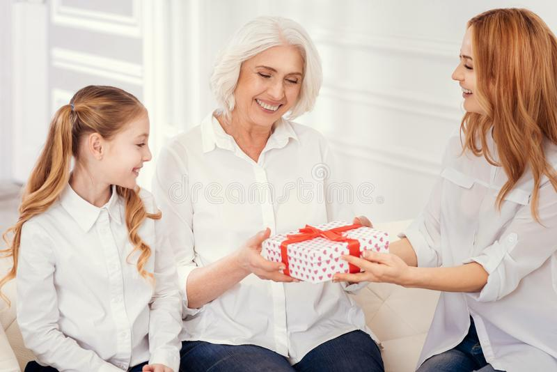 Loving mother and daughter giving present to their beautiful granny stock images
