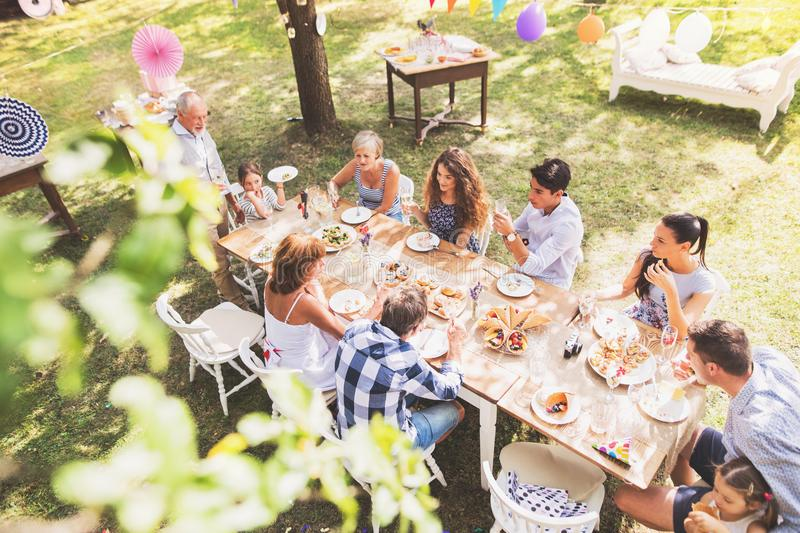 Family celebration or a garden party outside in the backyard. Family celebration outside in the backyard. Big garden party. High angle view royalty free stock photo