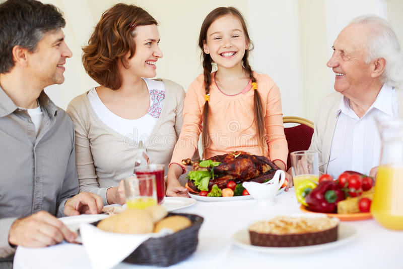 Family celebration. Happy family sitting at Thanksgiving table and looking at cute girl with roasted turkey royalty free stock photo