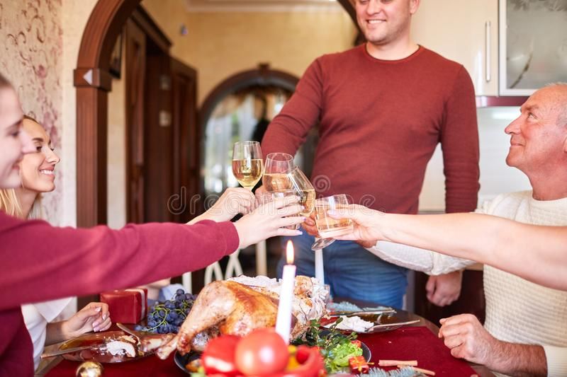Family cheering and drinking on Thanksgiving on a blurred background. Family holiday gathering concept. royalty free stock images