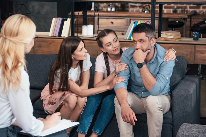 Family cheering up man on therapy session by female psychiatrist. In office royalty free stock photography