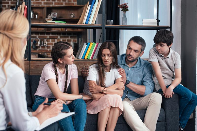 Family cheering up woman on therapy session by female counselor. In office stock image