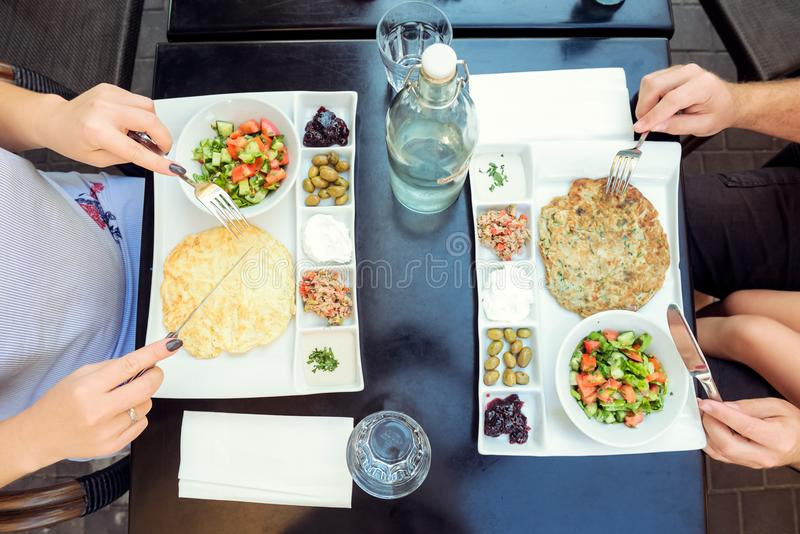 Family with child having traditional Israeli breakfast in the morning in cafe. Each portion with Eggs omelet, vegetable salad, sna stock photography