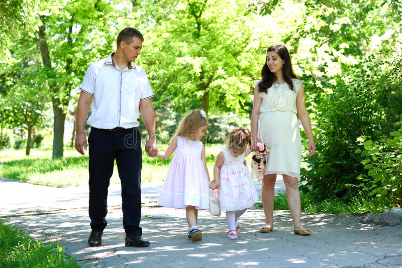 Family with child and pregnant woman walk in summer city park royalty free stock photography
