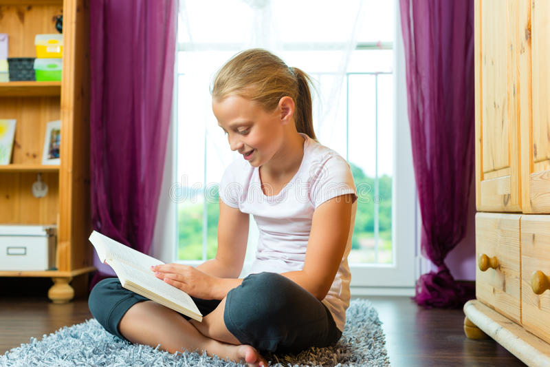 Family - child or teenager reading a book. At home in the living room royalty free stock images