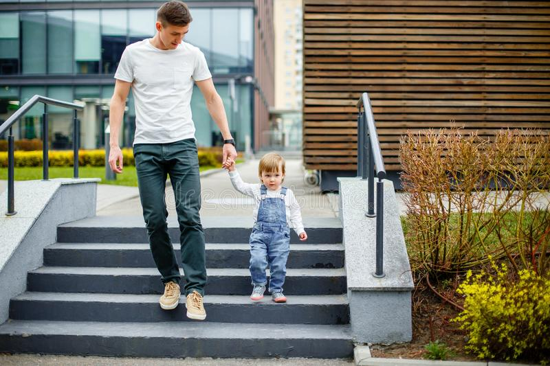 Family, childhood, fatherhood, leisure and people concept - happy young father and little daughter stroll through the streets of t stock photos