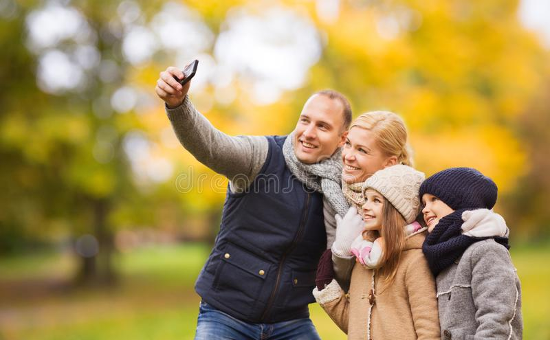 Happy family with camera in autumn park royalty free stock photo