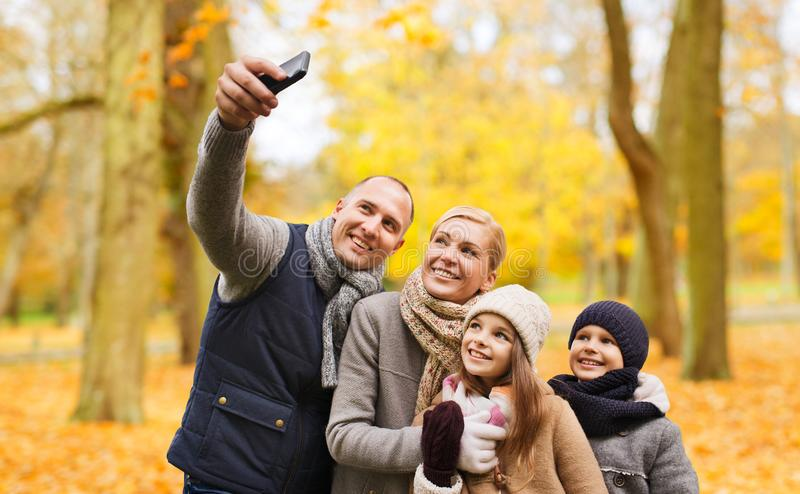 Happy family with camera in autumn park stock photo