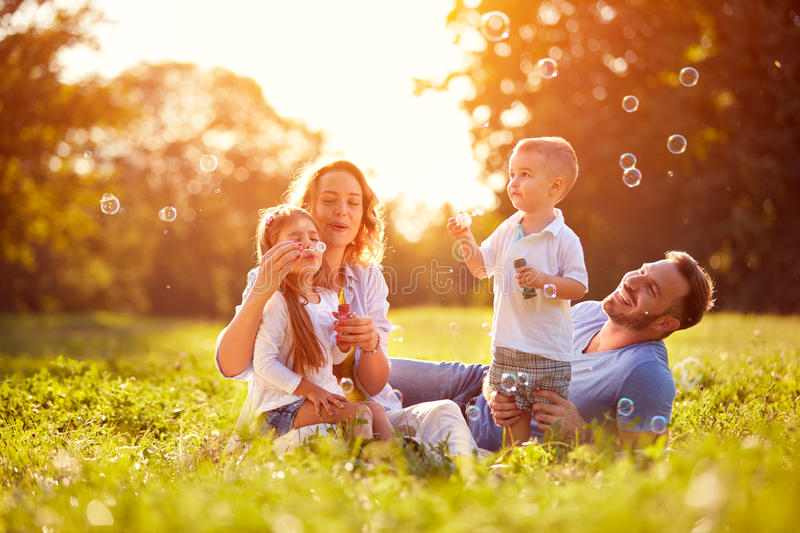 Family with children blow soap bubbles. Outdoor stock photo