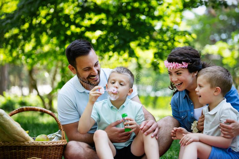 Family with children blow soap bubbles outdoors. Happy family with children blow soap bubbles outdoor royalty free stock photos