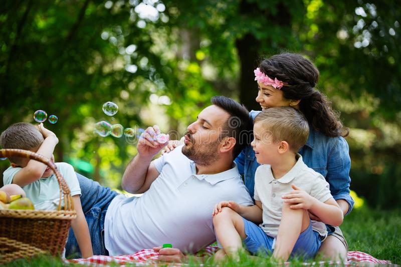 Family with children blow soap bubbles outdoors. Happy family with children blow soap bubbles outdoor stock photo