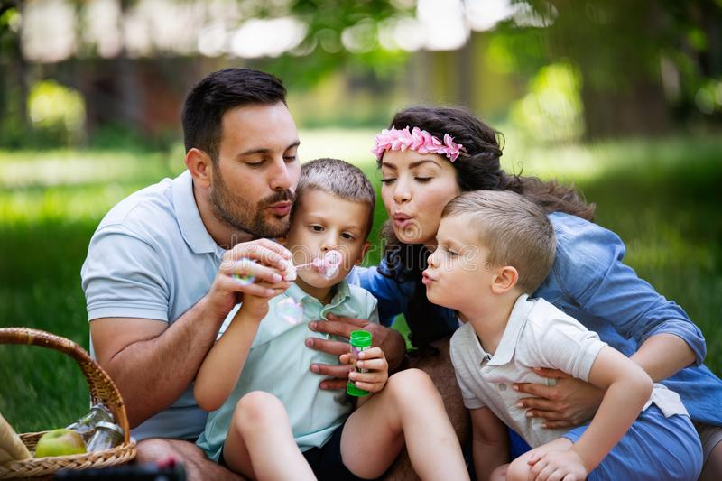 Family with children blow soap bubbles outdoors. Happy family with children blow soap bubbles outdoor stock photos