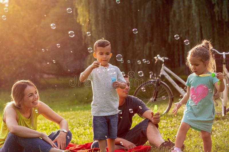 Family with children blow soap bubbles in park. Family with little children blow soap bubbles in park stock photos