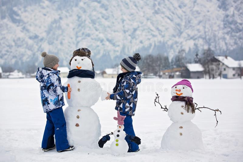Family with children, building snowman in the park in little village in Austria royalty free stock images
