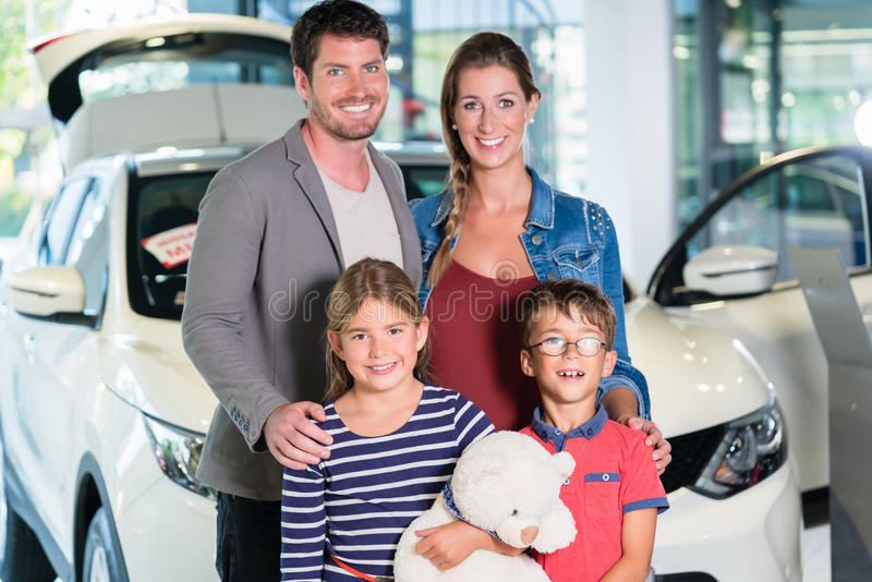 Family with children buying new car at auto dealership. Mom, dad and kids standing in showroom royalty free stock photography