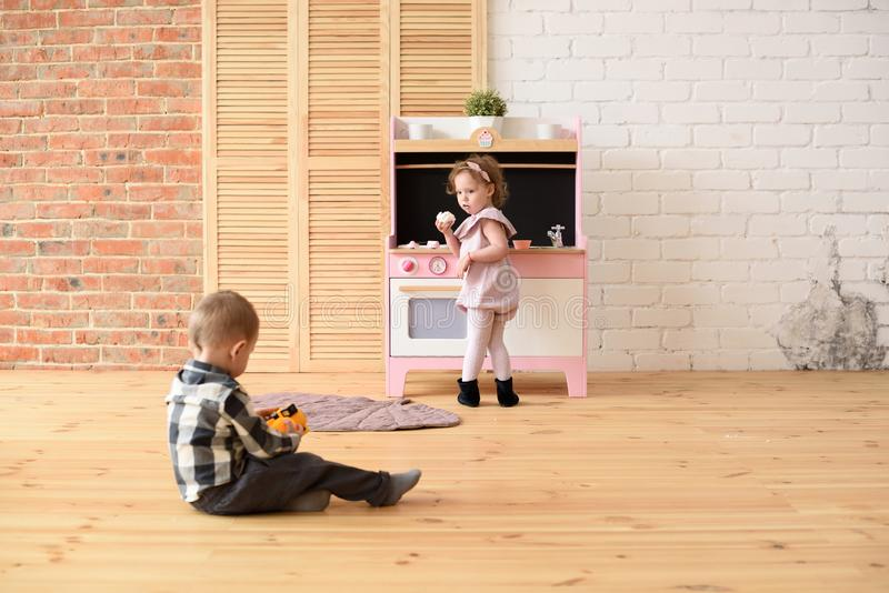 Family and children concept. Toddler boy playing on floor and cute little girl eating sweets at play kitchen in big empty room royalty free stock photos
