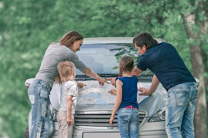 Family with children discusses a paper card during a family trip stock image