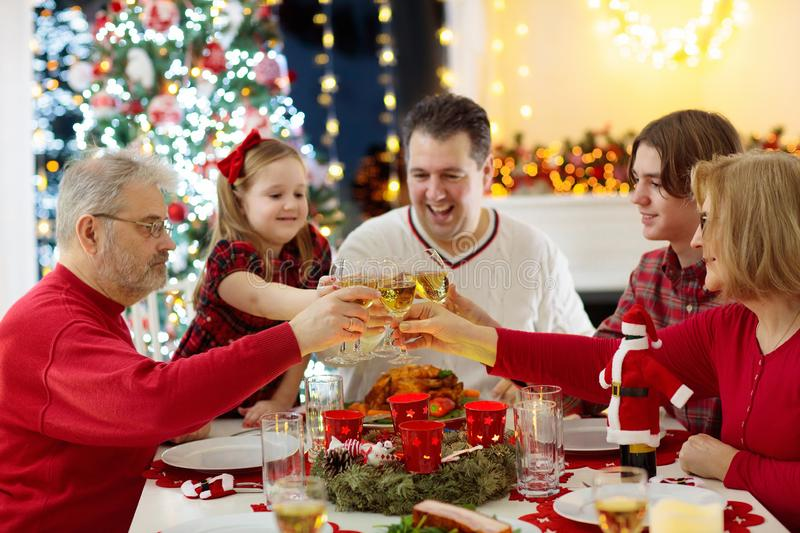 Family with children eating Christmas dinner at fireplace and decorated Xmas tree. Parents, grandparents and kids at festive meal. Winter holidays celebration royalty free stock photos