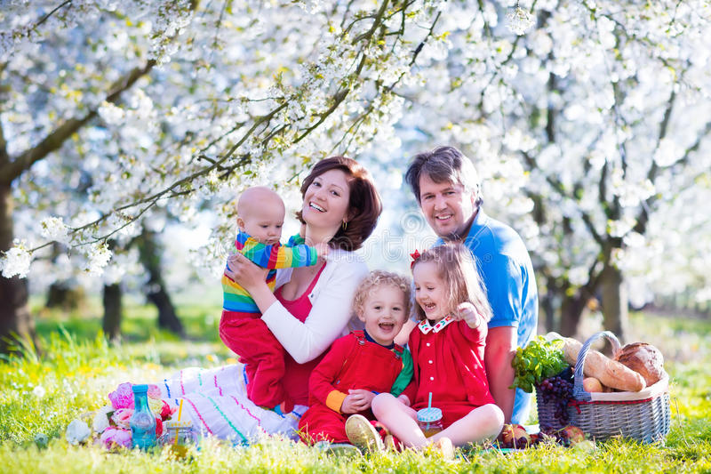 Family with children enjoying picnic in spring park. Big family with three little children eating lunch outdoors. Parents and kids with picnic basket in spring royalty free stock photography