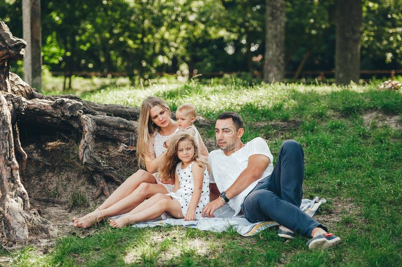 Family with children enjoying picnic in summer forest. Parents and kids having fun rest outdoors on green meadow. Mother, father and two little daughters lie royalty free stock photos