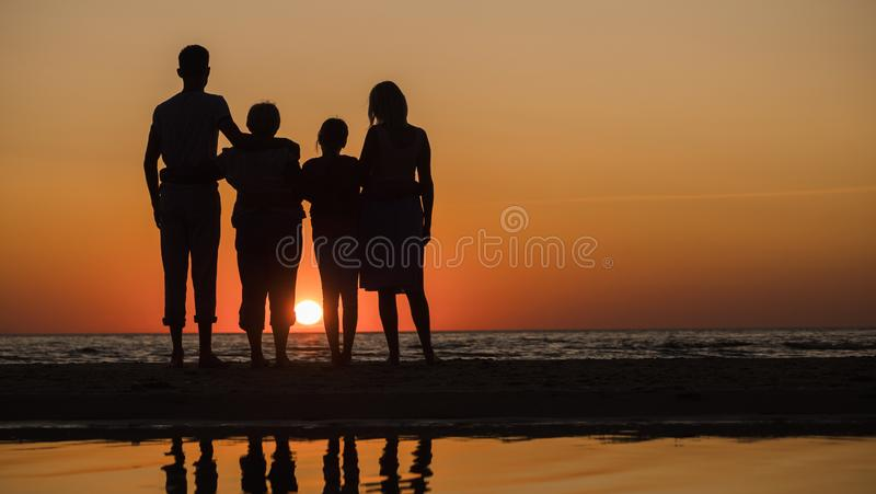 Family with children and grandmother somtry together at sunset over the sea stock images