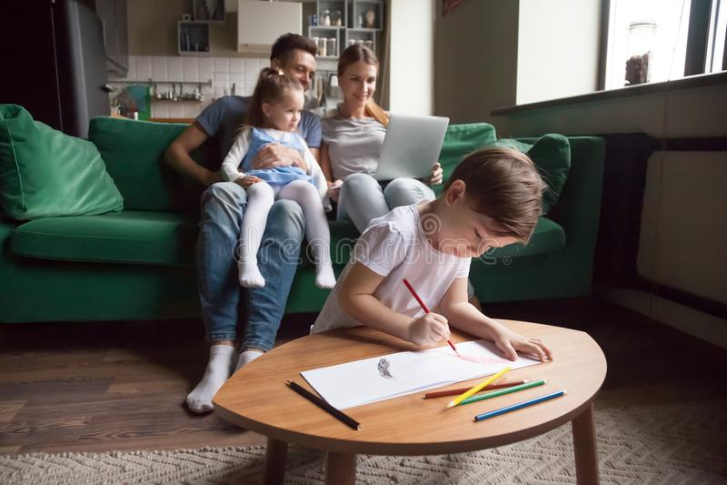 Family with children hobbies and activities at home on weekend. Creative kid boy son playing drawing with colored pencils while parents with little girl sister royalty free stock photos
