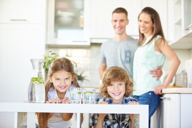 Family and children in kitchen. Happy family and two children in kitchen with fresh lime water stock images
