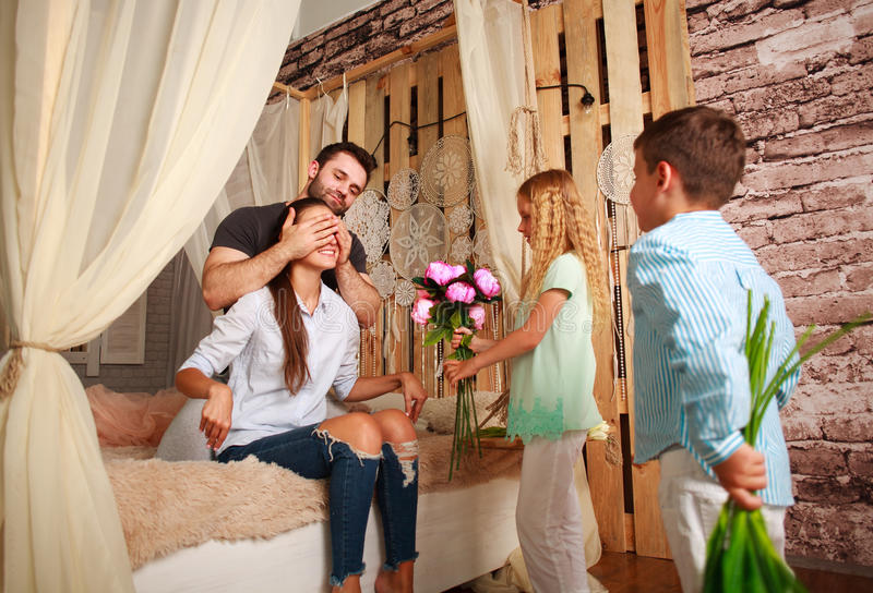 Family makes surprise mother giving presents of flowers royalty free stock photos