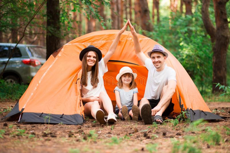 Family with children making arms roof promise protection forever. New building house purchase concept. Stylish full family with kid sitting near tent in forest royalty free stock photos
