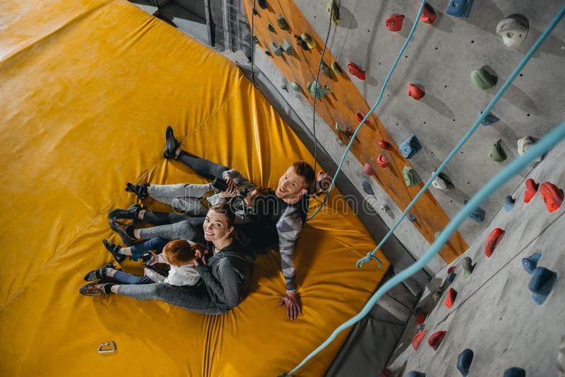 High angle shot of family with children. Sitting on a mat at gym with climbing walls in the background stock photography