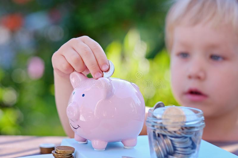 Piggy bank and little boy with coin on colorful background, close up stock photos