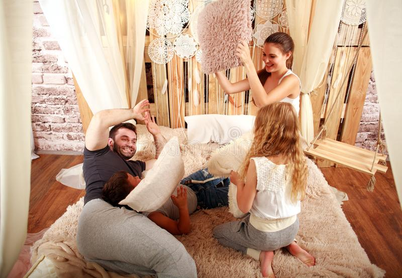 Family with children playing with pillows at home on bed royalty free stock photo