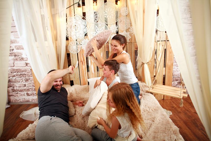 Family with children playing with pillows at home on bed stock images