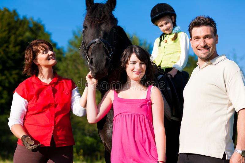 Family and children posing with horse stock images
